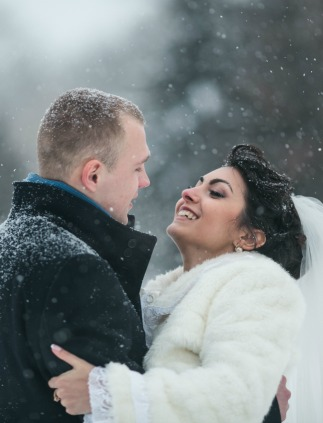 Bride and groom in snow for winter wedding photos