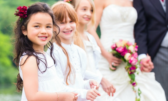 Three young girls standing with the bride and groom at a wedding