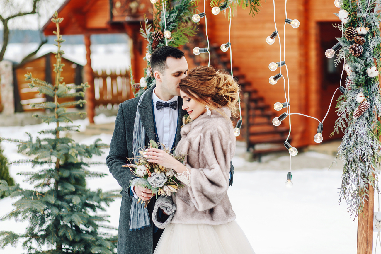 beautiful winter wedding - groom kissing bride during photoshoot