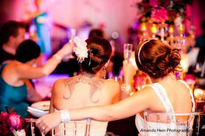 Two brides sitting together during their wedding reception. Amanda Hein Photography.