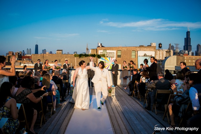 Two brides walking down the aisle together after the ceremony. Steve Koo Photography.
