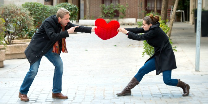 Angry couple fighting over a heart-shaped pillow
