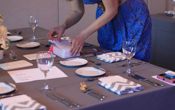 One of Heather Vickery's team members puts the finishing touches on a tablescape. Husar Photography.