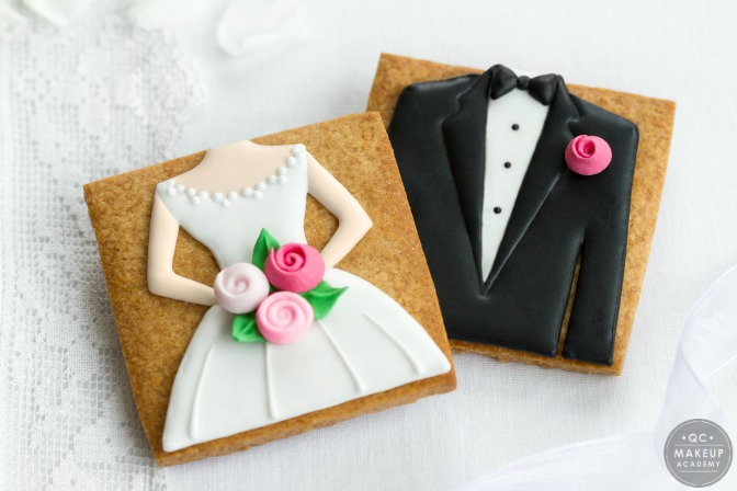 cookie decorated with bride and groom icing