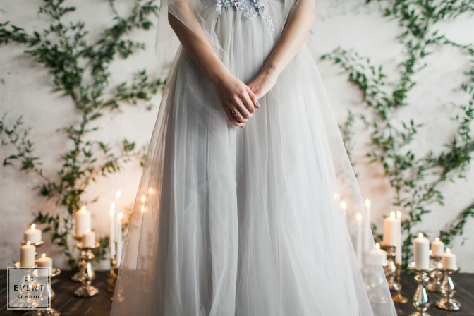 bride in wedding gown surrounded by softly lit pillar candles