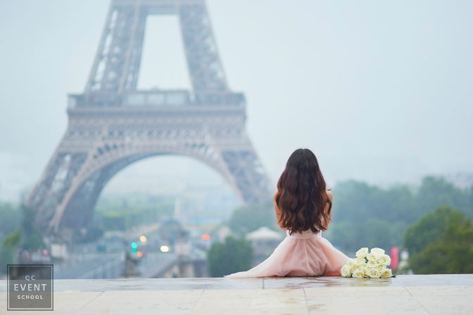 girl sitting in front of the Eiffel tower for a destination wedding photo shoot