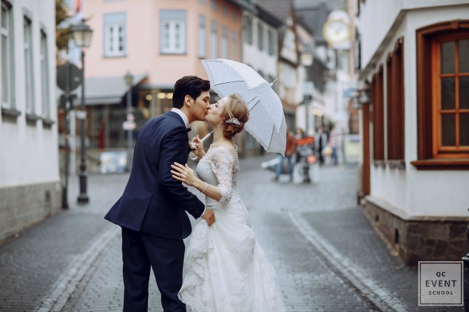 bride and groom standing under an umbrella at a rainy wedding