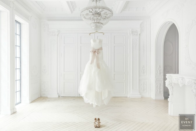 wedding gown hanging from chandelier