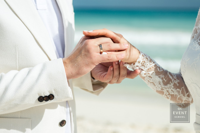 Marriage ceremony by the beach as the groom puts the ring on the brides finger