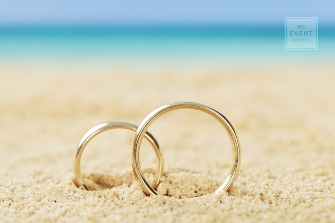 wedding rings together in sand at a destination wedding