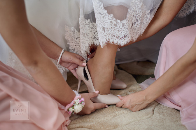 helping bride into her shoes wedding planning help