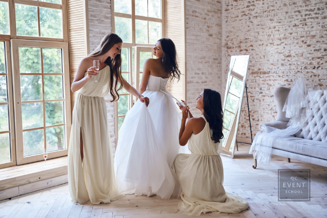 bride trying on wedding dress with her bridesmaids