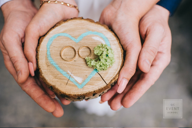 wedding couple with wedding rings on wood - career in wedding planning