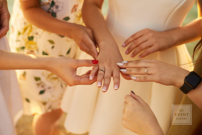 bride-to-be with engagement ring surrounded by bridesmaids and women
