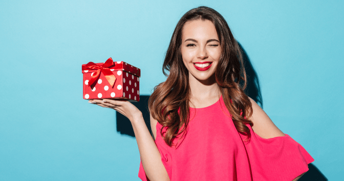 gifts for your event planner - woman winking and holding a wrapped gift