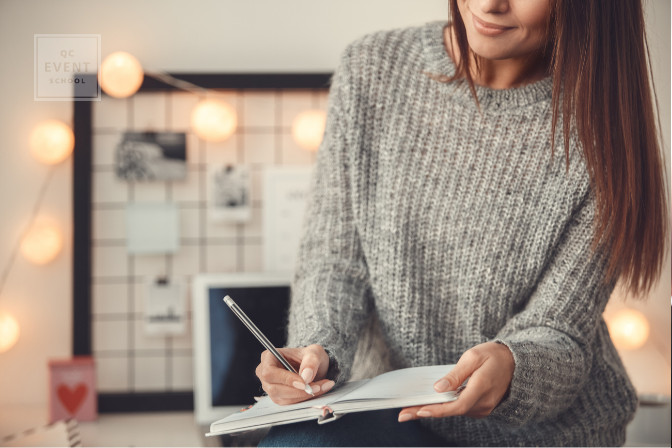 female event planner happily writing in planner