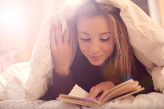 happy woman reading under a big blanket