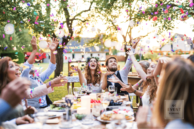 wedding party laughing and throwing confetti at table