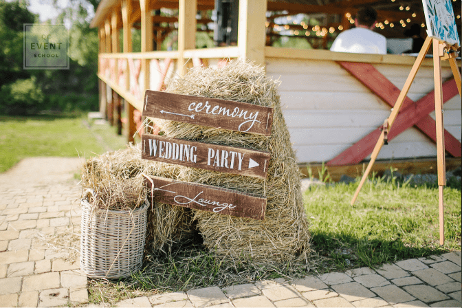 outdoor southern wedding decor - signs on a barrel with hay