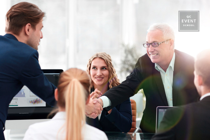 business meeting event planner shakes clients hand