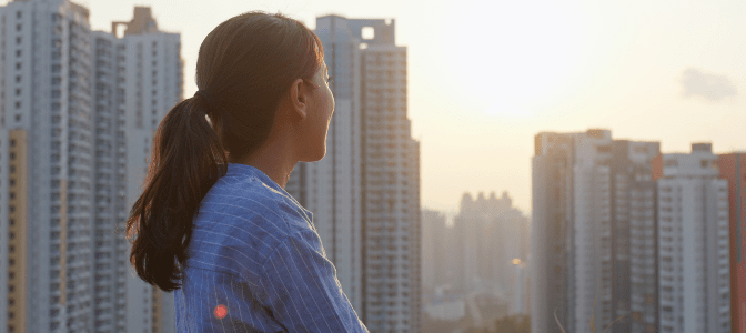 woman staring out at city landscape at sunset