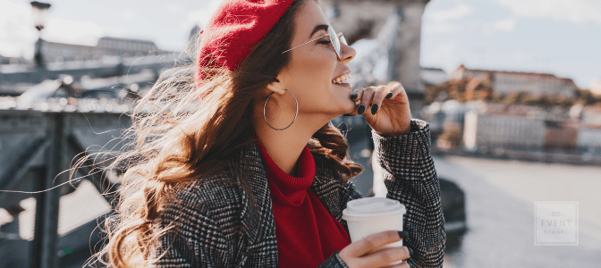 happy woman standing on bridge, drinking coffee, with wind blowing through her hair