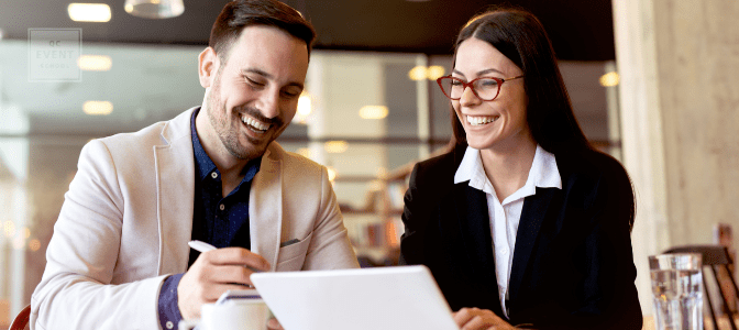 corporate event planner laughing at desk with client