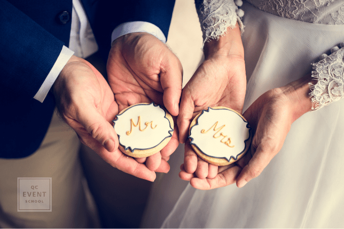bride and groom's hands, holding Mr. and Mrs. cookies