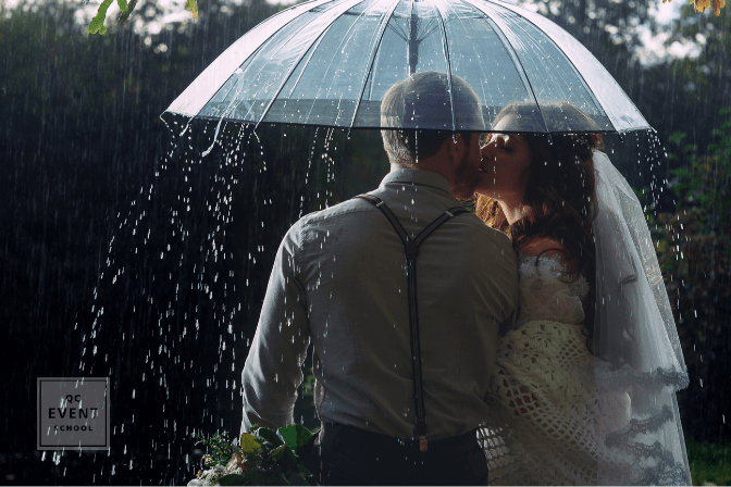 bride and groom kissing under umbrella while it rains
