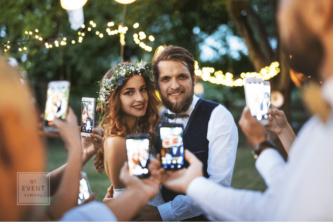 guests with smart phones taking photos of bride and groom
