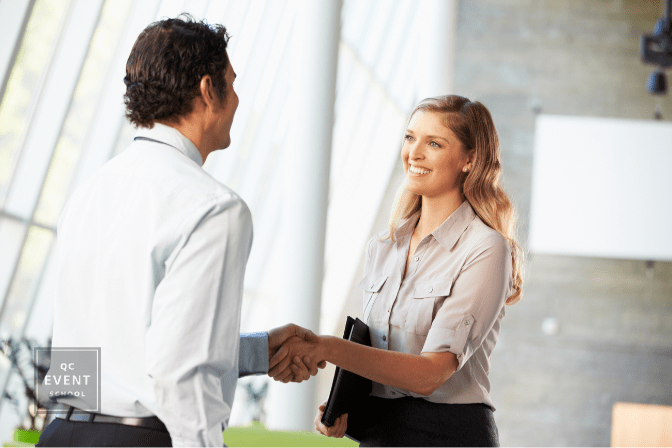 female corporate planner happily shaking hand of new business client