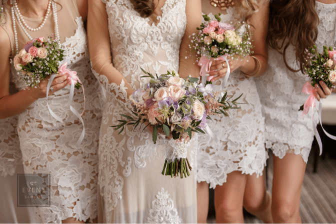 midriff shot of bride and bridesmaids in dresses and holding bouquets