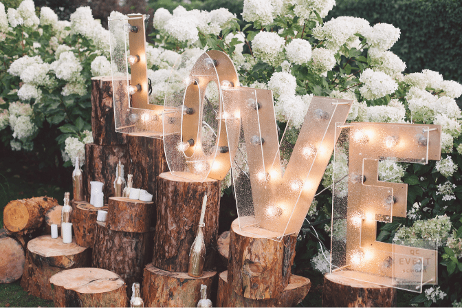 wedding decor - logs, flowers, and LOVE sign