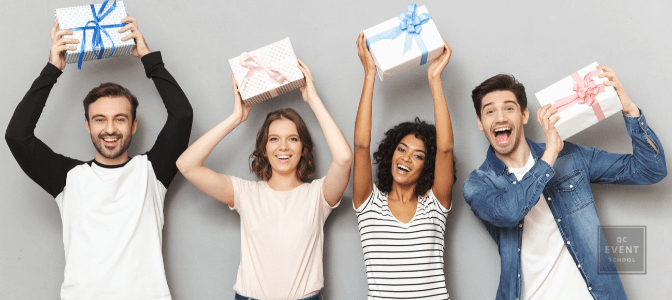 Image of excited group of friends standing isolated over grey wall background holding surprise gift boxes.