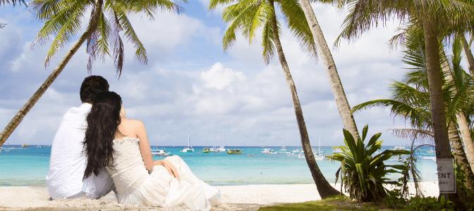 bride and groom on beach looking at ocean