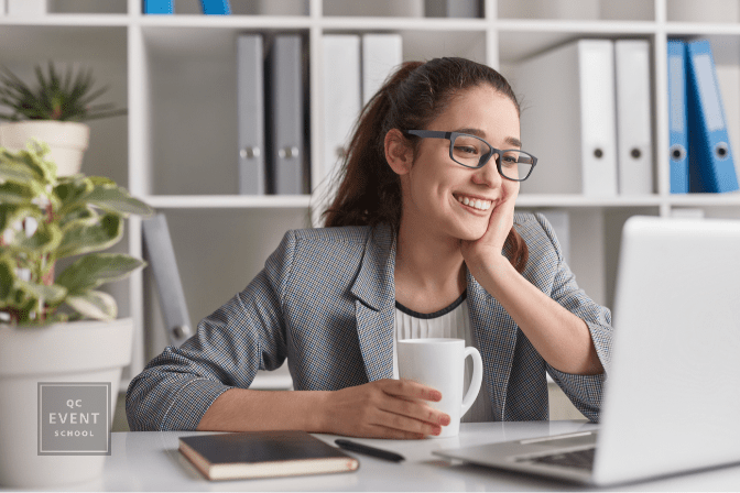Happy young woman smiling and using laptop while enjoying fresh coffee at desk in morning at work