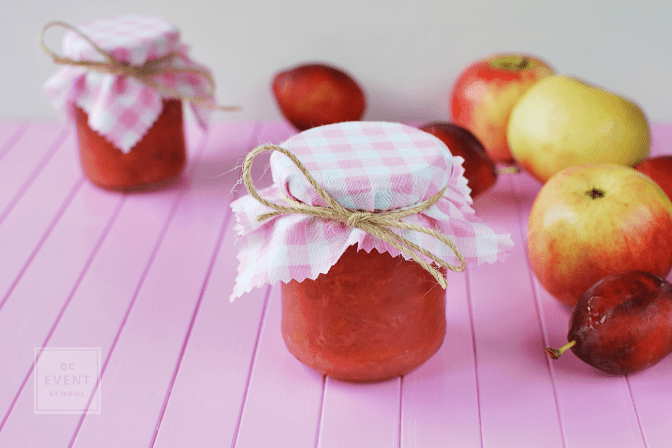 Decorated mini jars of jam, rustic wedding favors. Apple and plum jam, pink background, space for text.
