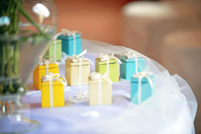 Brightly colorful little party favors in the form of decorative gift boxes tied with bows on a table at a special event or reception