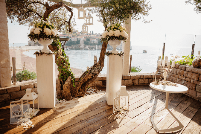 destination wedding ceremony arch with sea view and olives at sunset