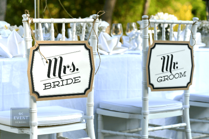 bride and groom chair with signs on back