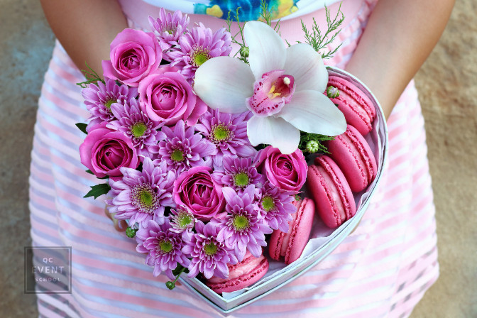 flowers and sweets in a box in the shape of a heart in the hands of the girl in the pink skirt closeup with blurred background. White Orchid, pink roses, pink chrysanthemums, pink macaroons