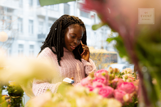 florist watering flowers while speaking on the phone