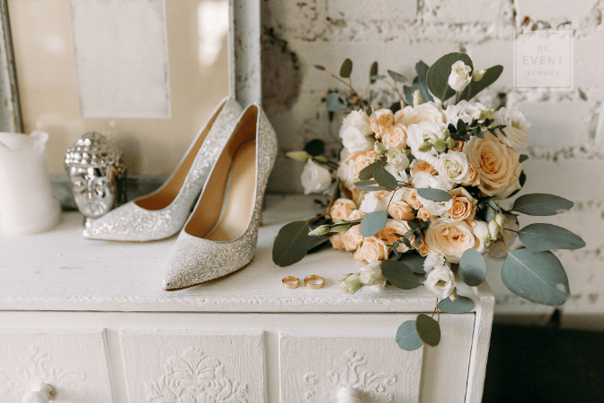 bride's shoes and bouquet on top of white dresser at wedding