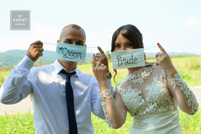 bride and groom holding up face masks at wedding