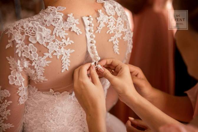 certified wedding planner doing up back of bride's dress
