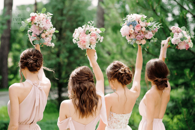 bridesmaids holding up bouquets outside