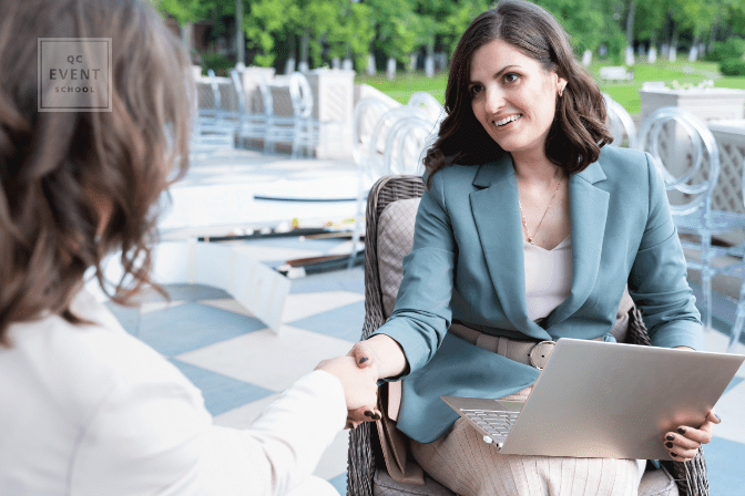 event planner shaking hands with client at venue