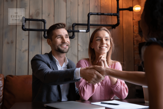 excited couple shaking event planner's hand