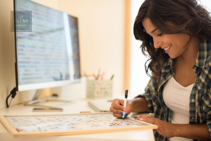 Woman sitting at desk, filling out calendar board