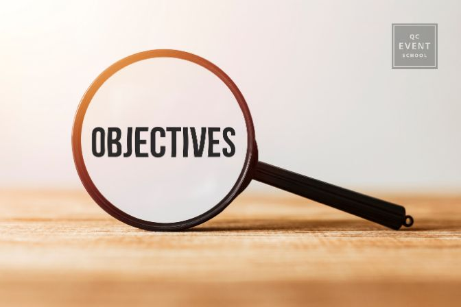 """Objectives for event planning company article first in-post image, magnifying glass with word """"Objectives"""" in it"""